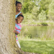 African sister and brother peeking out from behind tree in park — Stock Photo #23270822