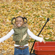 African girl playing with wagon in autumn leaves — Stock Photo #23270834