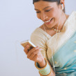 Indian woman in traditional clothing using mp3 player — Stock Photo