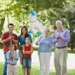 Hispanic family watching boy hit pinata — Stock Photo