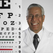 Portrait of Indian male doctor holding eye chart — Stock Photo