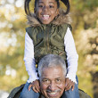 African grandfather carrying granddaughter on shoulders — Stock Photo