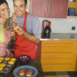 Hispanic couple icing cupcakes in kitchen — Stock Photo