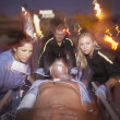 Doctors wheeling emergency patient on gurney outdoors at night — Stock Photo