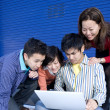Group of young businesspeople looking at laptop — Stock Photo