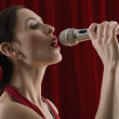 Hispanic female singing into microphone — Stock Photo