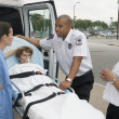 Female doctor talking to EMTs with boy on gurney — Stok fotoğraf