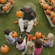 African man talking to children about pumpkins — Stock Photo