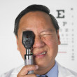 Asian male optometrist looking through medical instrument — Stock Photo