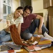 Hispanic couple looking at textile swatches in new house — Stock Photo #23271108