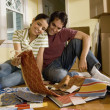 Stock Photo: Hispanic couple looking at textile swatches in new house