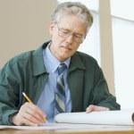 Businessman writing on paperwork — Stock Photo