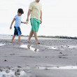 Hispanic father and son walking on beach with starfish — Stock Photo