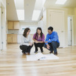 Asian couple looking at blueprints in new house — Stock Photo