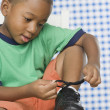 Young African boy tying shoe - Stock Photo
