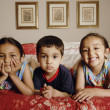 Portrait of Indian brother and sisters on bed — Stock Photo