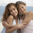 Stock Photo: Two teenage girls hugging at beach