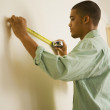 African man using tape measure on wall — Stock Photo