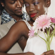 African couple hugging and holding daisies — Stock Photo