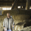 Portrait of male farmer in hay barn — Stock Photo