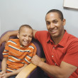 African father and son in waiting room — Stockfoto