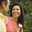 Hispanic man giving wife gift outdoors — Stock Photo