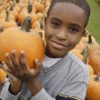 Portrait of African boy holding pumpkin — Stock Photo
