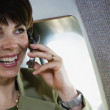 Businesswoman using cell phone on private airplane — Stock Photo #23271486