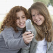 Two teenage girls using camera phone outdoors — Stock Photo