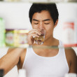 Asian man drinking glass of water — Stock Photo
