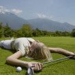 Woman laying on golf course with golf club and golf ball — Stock Photo
