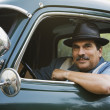 Middle-aged Hispanic man sitting in classic car - Stock Photo