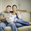 Asian couple sitting on sofa with popcorn — Stock Photo