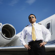 Asian male pilot standing near airplane — Stock Photo