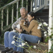 Couple with dog sitting on porch steps — Stock Photo