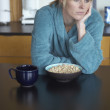 Stock Photo: Unhappy womsitting at breakfast table