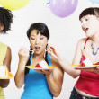 Three women eating cake at party — Stock Photo