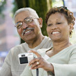 Senior African couple taking self-portrait in park — Stock Photo