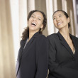 Two businesswoman laughing next to columns — Stock Photo