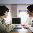 Businessman and businesswoman using laptop on private airplane — Stock Photo