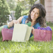 Hispanic woman looking at shopping bags in grass — Stock Photo