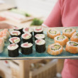 Stock Photo: Womholding tray of sushi