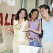 Hispanic women shrugging shoulders next to shop with sale sign — Stock Photo