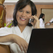 Asian woman in spa bathrobe using cell phone and laptop — Stock Photo #23272026