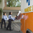Paramedics putting woman into ambulance — ストック写真