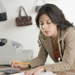 Hispanic businesswoman paying bills at boutique — Stock Photo #23272064