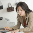 Stock Photo: Hispanic businesswompaying bills at boutique