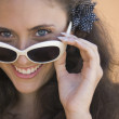Close up of young woman smiling over top of sunglasses — Stock Photo