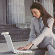 Businesswoman typing on laptop in front of building — Stok fotoğraf