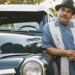 Middle-aged Hispanic mleaning against classic car — Stock Photo #23272142